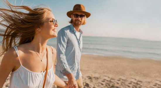 young attractive smiling happy man in hat and blond woman running together on beach on summer vacation traveling, romantic couple by the sea on sunset, boho hipster style outfit wearing sunglasses, friends having fun together
