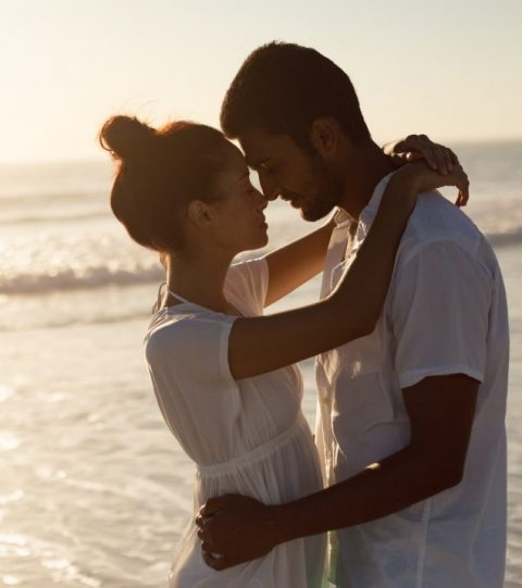 A man and woman embracing on a beach at sunset